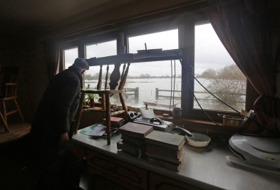 Somerset farmer, 66-year-old Bob Hall, stands in his flooded kitchen as he loads some of his processions onto a tractor trailer as he prepares to leave his property that flooded this morning in Fordgate.